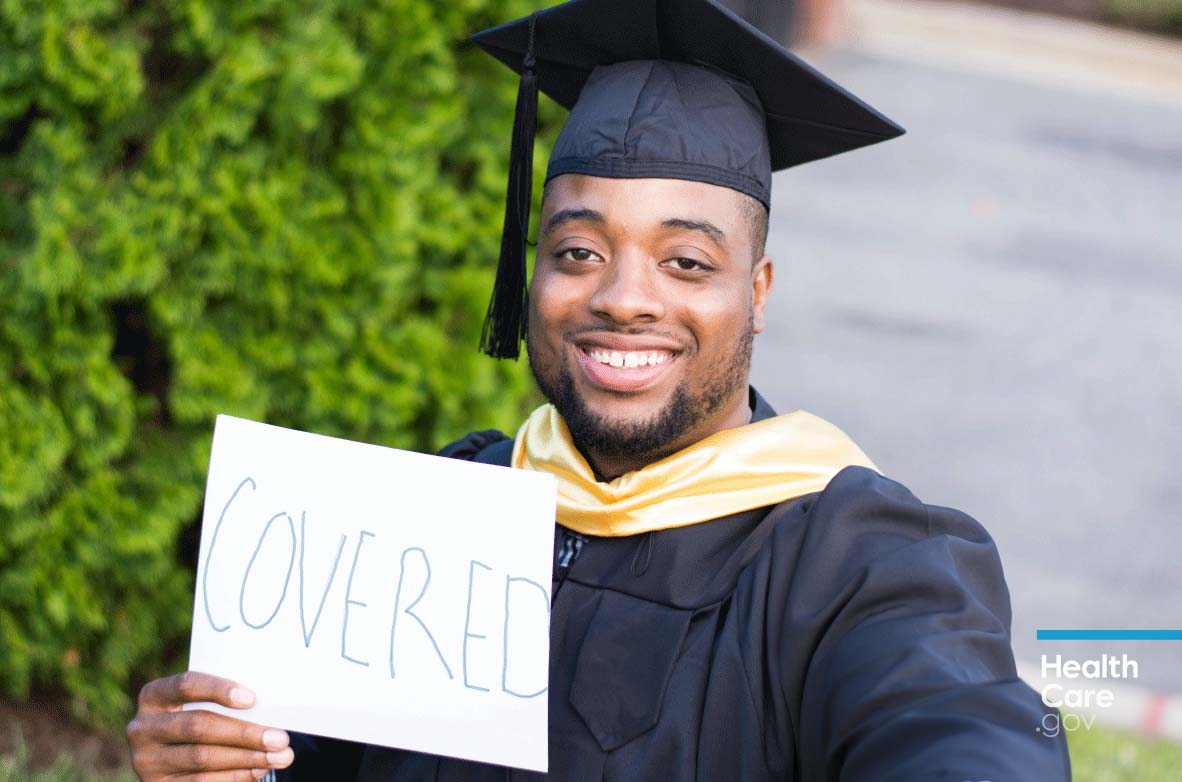 Image: {Graduate holding sign saying he has young adult health insurance coverage}